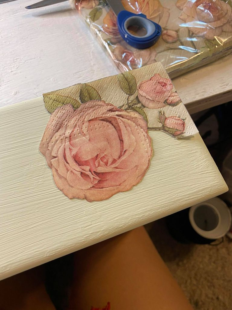 cutting out pieces of a rose napkin to use for decoupaging a vanity drawer