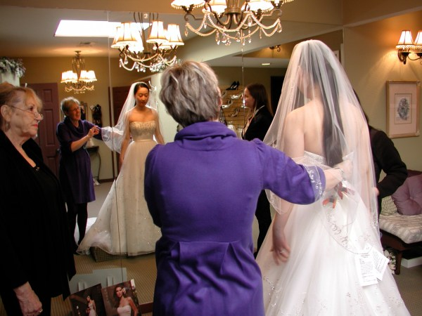 Denise Fehler, owner of Cynderellies Closet, admires the dress being worn by Amy Liu of Bothell, who is planning a fall wedding and stopped by the Edmonds bridal boutique Saturday morning.