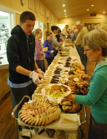 Guests make their way through the food line with help from volunteers. (2012 file photo by Mary Coughlin)