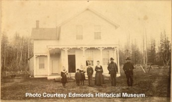 George Brackett family in front of residence, c. 1890, Location of what is corner of 2nd Ave N & Edmonds Street.  L to R: Nellie, Ronald, Fannie, George Jr., Etta & George Brackett, unknown.