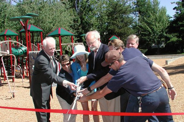 Those cutting the ribbon included volunteer leader Richard Marin, Parks Director Carrie Hite, City Councilmember Joan Bloom, Mayor Dave Earling and parks employees Katrina Harris and Rob Freeborn (in dark blue shirts). In the back is Parks Manager Rich Lindsay.