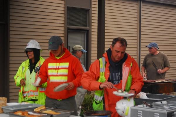 Calvary Chapel of Edmonds, which is located at Five Corners, hosted an appreciation lunch Friday for the work performed by the crew putting in the roundabout.  Chapel pastor Scott Vincent, in brown shirt, can be seen behind the barbecue at the right. (Photos by Ken Sjodin)