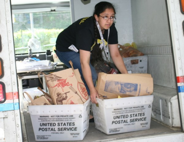 Rumneet Grewal, of Everett, helps unload food donations from a mail truck.