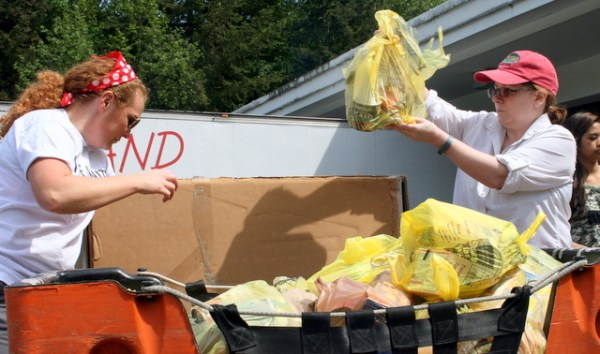 Krista Holcepl, of Marysville, and Kim Conant (right), of Edmonds, sort through food donations during the annual annual Letter Carriers Food Drive on Saturday. Holcepl and Conant were among many volunteers at the Perrinville Post Office facility in Edmonds.