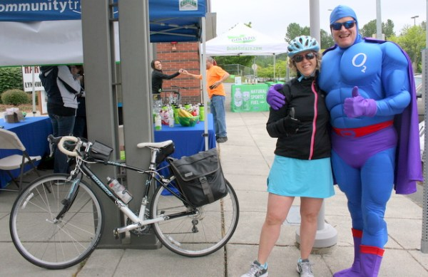 Barbara Wilds (left), of Edmonds, was the 100th cyclist to stop by a special Commuter Station at the Lynnwood Transit Center during Bike to Work Day on Friday. She is congratulated by Community Transit's Oxy Gene. Wilds rides her bike to work in Lynnwood. (Photo by David Pan)