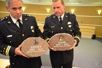 Assistant Chiefs Lawless and Anderson hold up the granite markers for late K-9 officers Rocky and Dash.