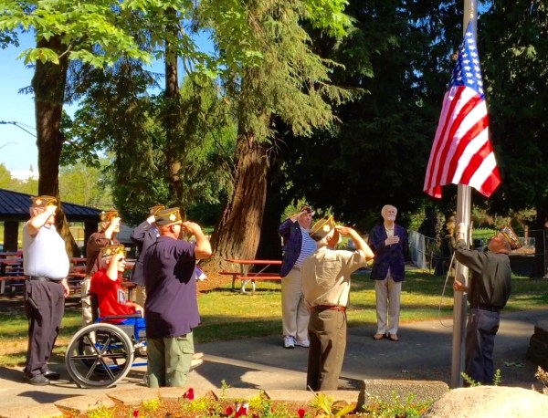 Old Glory proudly rises toward the top of the flagpole at Edmonds City Park on Sunday as members of Edmonds Post 8870 of the VFW render honors. Left to right, Al Starkenburg, Phil Sacks, John Shelton, Mike Denton (partially obscured), Carl Kurfess, Post Commander James Blossey, Edmonds Mayor Dave Earling and Les Abel.