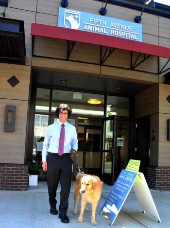 "Dr. Chris Garg greets Rocky, a 6-year-old Golden Retriever who dropped in for the open house.  Rocky, a certified therapy dog, is owned by Edmonds CPA John Weiss.  ""He's retired as a therapy dog, "" quipped Weiss.  ""He's a tax dog now!"""