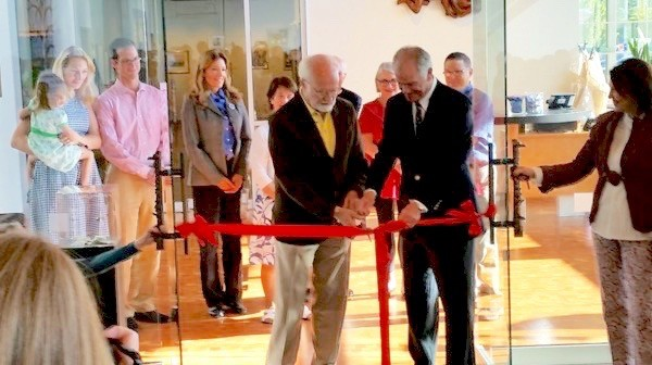 Mayor Dave Earling and Cascadia Art Museum President Lindsey Echelbarger cut the opening ribbon, with interim director Elizabeth Martin-Calder's assistance. In back from left: Caitlin and Nicholas Echelbarger with their daughter Helen, board member Janette Turner, Carolyn Echelbarger, board members Philip Grad, Marni Muir, and Gary Faigin.