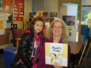 Jennapa Hodson, 7, a Westgate Elementary second-grader, visits with the author.