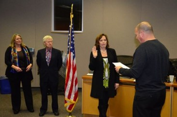 Superintendent Nick Brossoit administers the oath of office to Diana White as Gary Noble and Carin Chase look on.