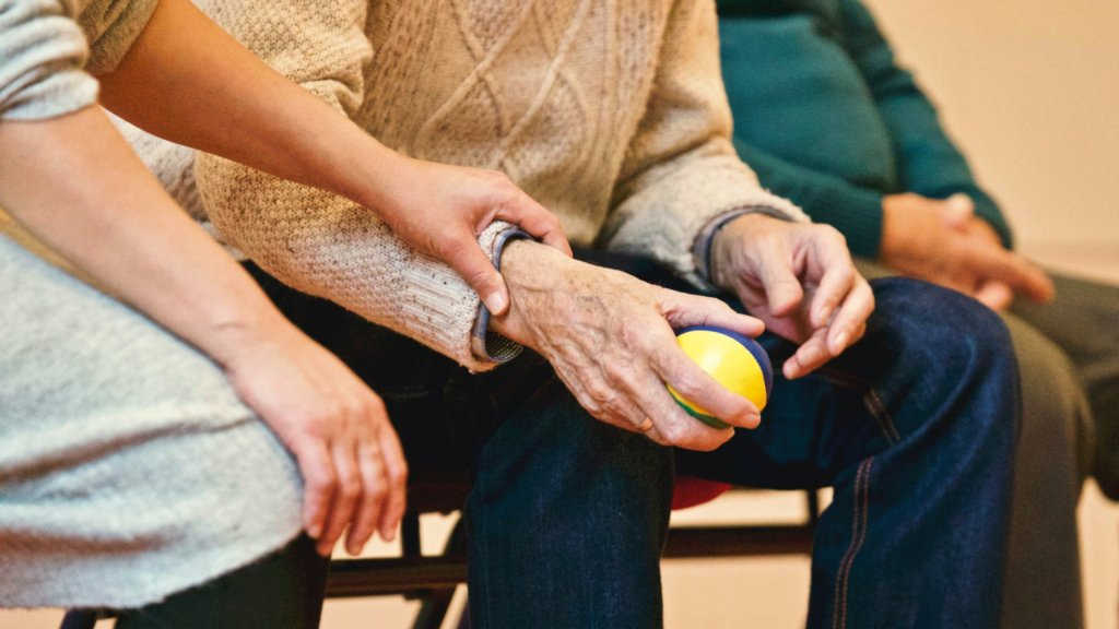 Elderly person holding a ball with doctor