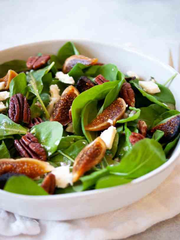 bowl of arugula salad with dried figs, pecans, and blue cheese