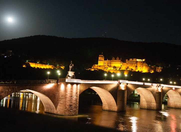 Landmark image of Heidelberg Castle with the old Heidelberg Bridge in the foreground on a night of a full moon.
