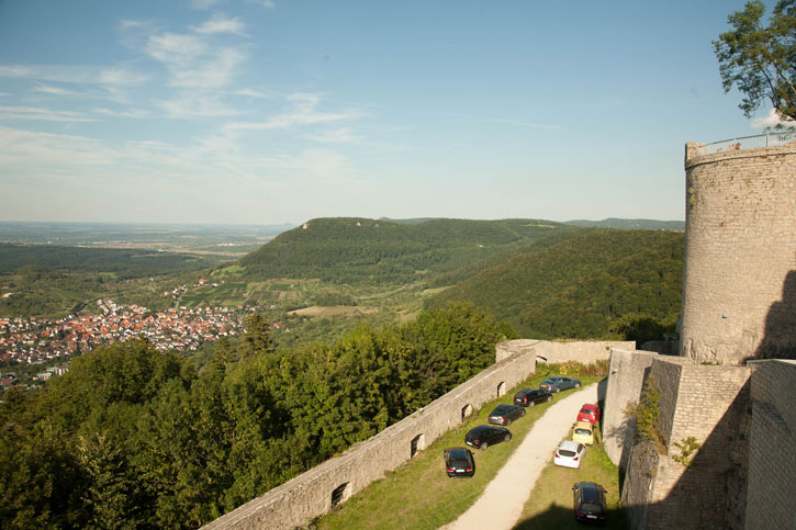 The hills around Neuffen town taken from Neuffen Castle. This road passage leads to the entrance is on a steep incline. It is next to a castle wall which overlooks people travelling up this passage. This is the passage that is before the entrance. It has a difficult bend described earlier. Many cars have parked here because of the difficulty turning the corner and getting up another steep incline within the castle.