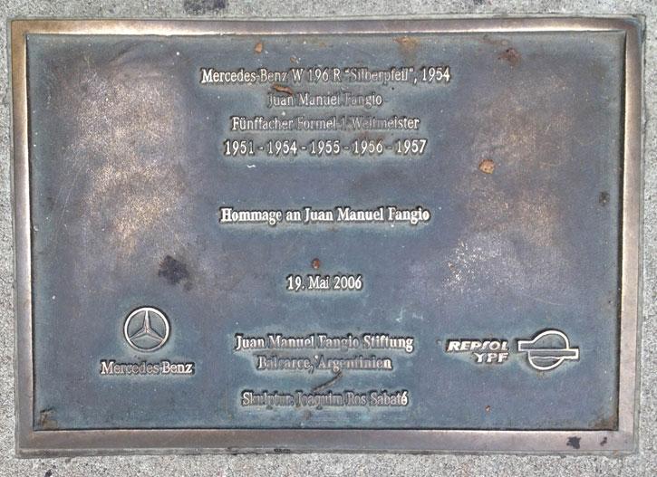 A bronze plaque commemorating the achievement of Juan Manuel Fangio.
