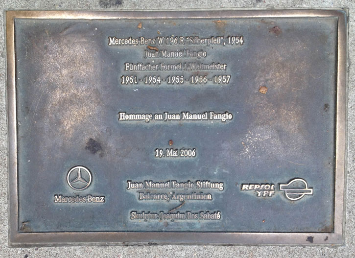 A bronze plaque commemorating the achievement of Juan Manuel Fangio.
