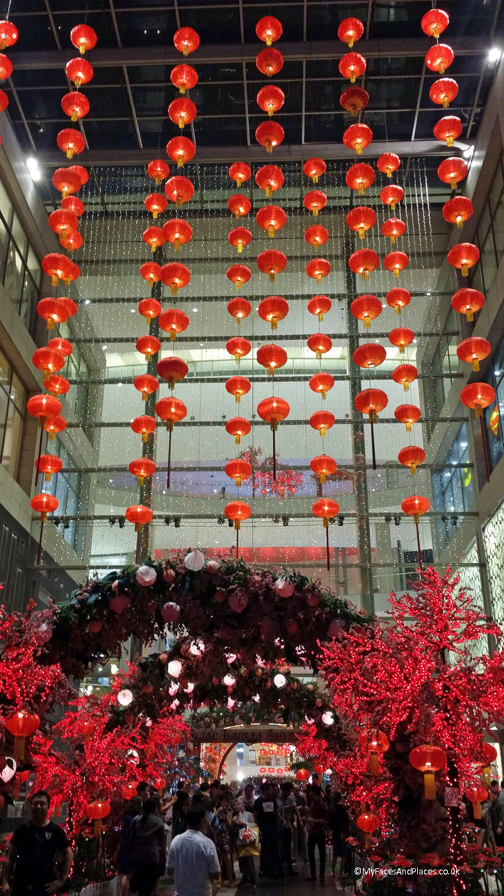 The Main entrance of the Pavilion Shopping Mall in Kuala Lumpur. It is bedecked with red Chinese lanterns with a floral arch of Chinese Peach and Chinese Plum Blossoms Trees as part of the Chinese New Year Celebrations.
