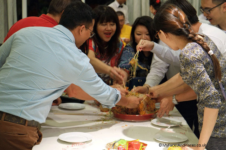 """Helen, as part of a group tossing the Yee Shan dish and raising a chorus of """"Lo Hai"""" for good fortune."""