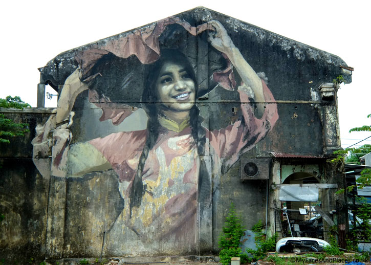 """The Hakka Dancing Girl"". Julia was mesmerised by the photograph of Pang Yi Chuen doing a ""merry twirl"" in a Hakka traditional dance. She painted it on the walls in this pre-dominantly Hakka village."