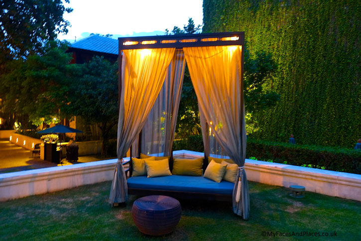 A romantic day bed for guests to relax in the garden of 137 Pillars House