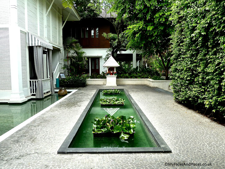 The serene entrance with lovely water lilies overlooked by a shrine in 137 Pillars House