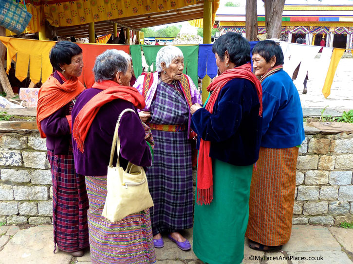 Women in colourful kira, their traditional national costumes at a religious ceremony - Bhutan the Beautiful