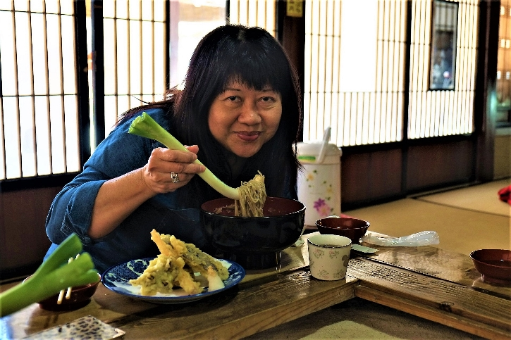 Helen Oon trying to master the traditional art of eating soba noodles with a stick of leek.