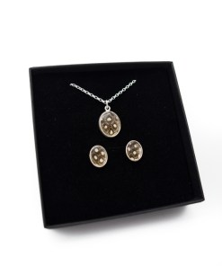 A three piece Guinea Fowl jewellery set. Contains one silver necklace with oval pendant and two matching earrings.