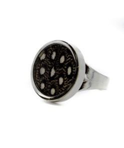 A single, round, rhodium plated ring, containing a black and white Guinea Fowl feather.