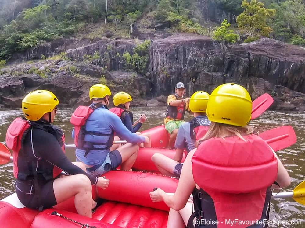 Group of people on a boat listening to a guide giving instructions on how what to do during their whitewater rafting tour in Cairns