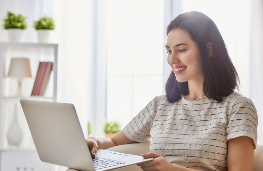 Woman smiling looking at laptop - How to make 10 dollars fast with PayPal-My Financial Hill