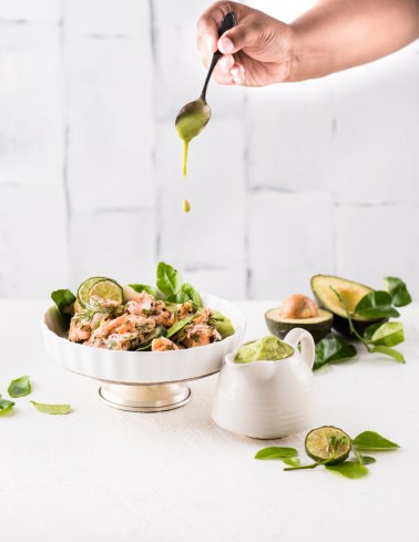 Cold salmon salad being drizzled by avocado dressing with lime leaves & lemongrass