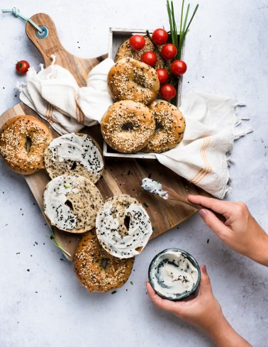 Action shot of a person spreading cottage cheese over sesame bagels served with cherry tomatoes