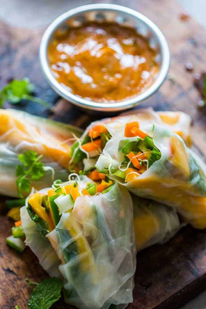 These mango bell pepper rice paper rolls are the perfect summer food! They are stuffed with lots of amazing veggies and come with an insanely delicious mango cilantro dipping sauce! These are naturally gluten free, vegan and low carb!