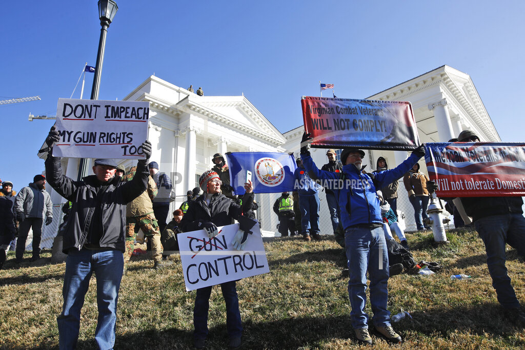This Monday an. 20, 2020 file photo shows pro gun demonstrators holding signs in front of the Virginia State Capitol in Richmond, Va. In a state once synonymous with the Old South, Democrats are using their newfound legislative control to refashion Virginia as the region's progressive leader on racial, social and economic issues. (AP Photo/Steve Helber)