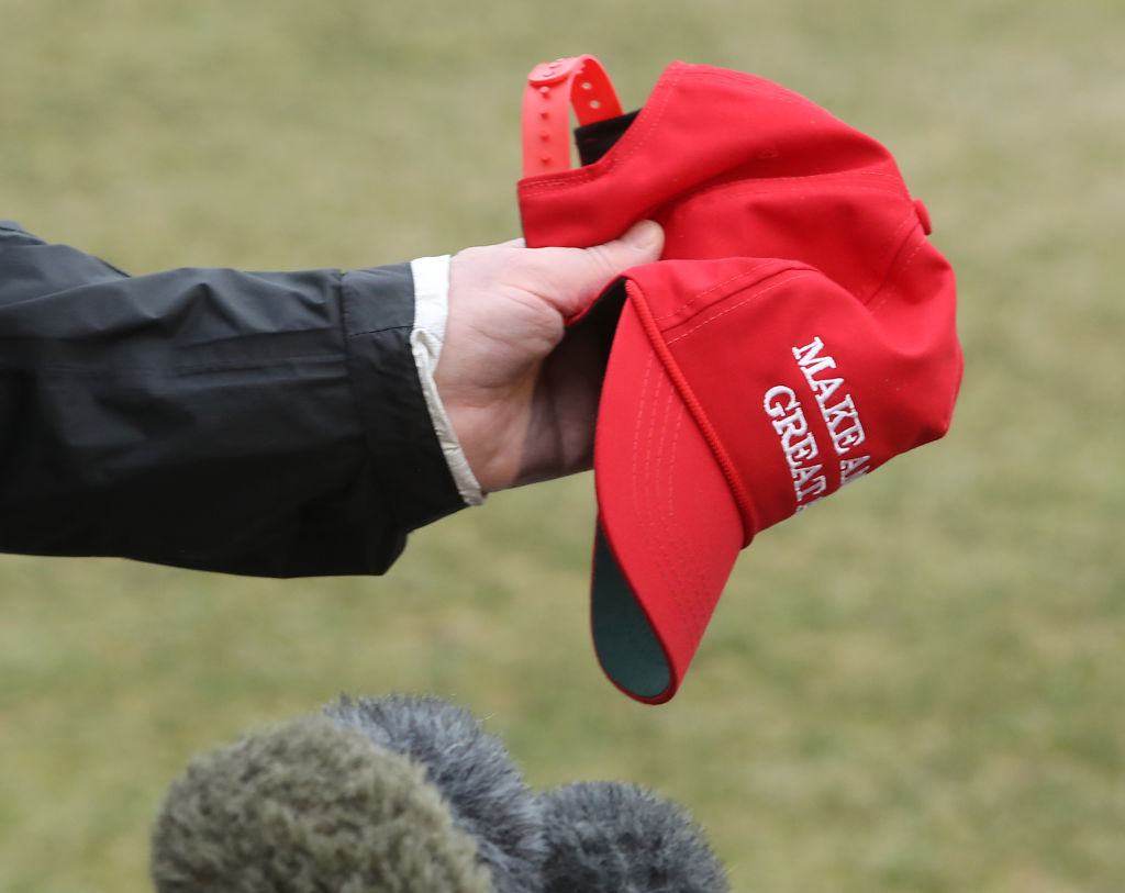 "U.S. President Donald Trump holds a ""Make America Great Again"" hat as he speaks to the media before departing from the White House on March 8, 2019 in Washington, DC. (Photo by Mark Wilson/Getty Images)"