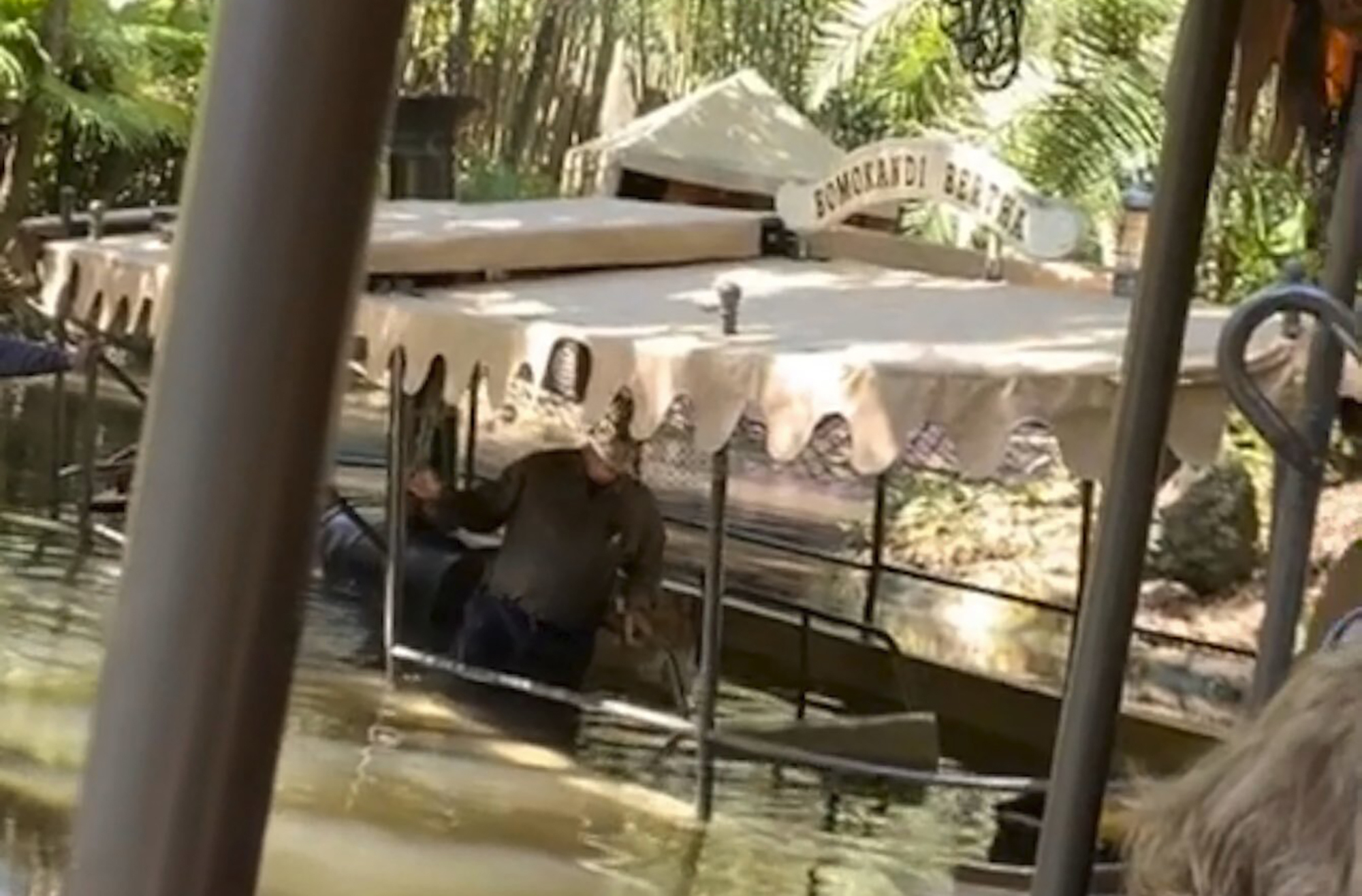 A person stands knee-deep in water aboard a Jungle Cruise boat after the vessel took on water, Thursday, Feb. 27, 2020, at Walt Disney World in Orlando, Fla. The boat was evacuated and no one was hurt. (Matthew Vince via AP)