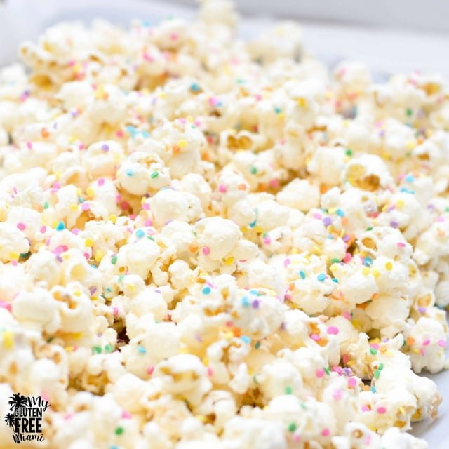 white chocolate popcorn drying on a sheet pan