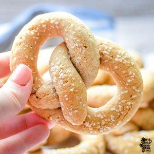 holding one gluten free soft pretzel