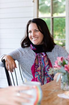 A woman sits in a chair with her arm up on the back. She wears a grey shirt and a Marilue Cowl in black.  She's threaded a pink scarf through the scallops of the cowl for a decorative look.