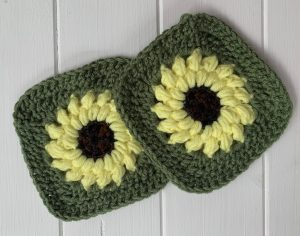 Two crocheted granny squares made with colors to look like sunflowers surrounded by green border
