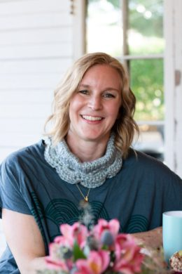 A woman smiles directly at the camera. She is wearing a mint colored Marilue Cowl folded in half an low on her neck like a chunky necklace.