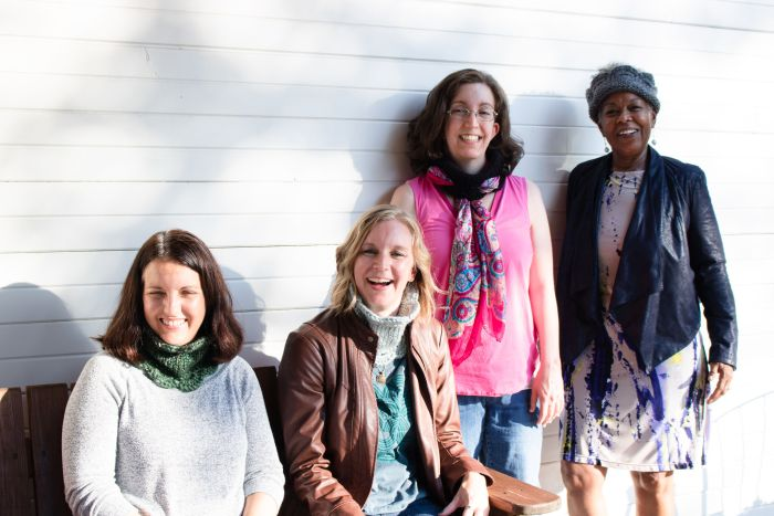 Four people are smiling at the camera. They are each wearing a Marilue Cowl in a different way. One wears a green tweed cowl flipped up over a grey shirt. The next wears a mint Marilue Cowl tucked into a brown leather jacket. A woman stands wearing a black Marilue Cowl with a silk scarf threaded through the scallops. Another stands wearing a purple leather jacket and a gray cowl folded in half and worn as an ear warmer.
