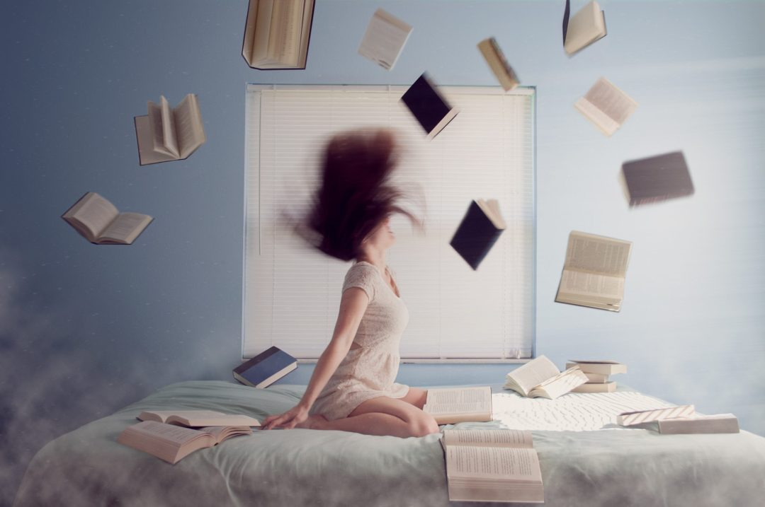 ritmo femme sur un lit livres qui volent