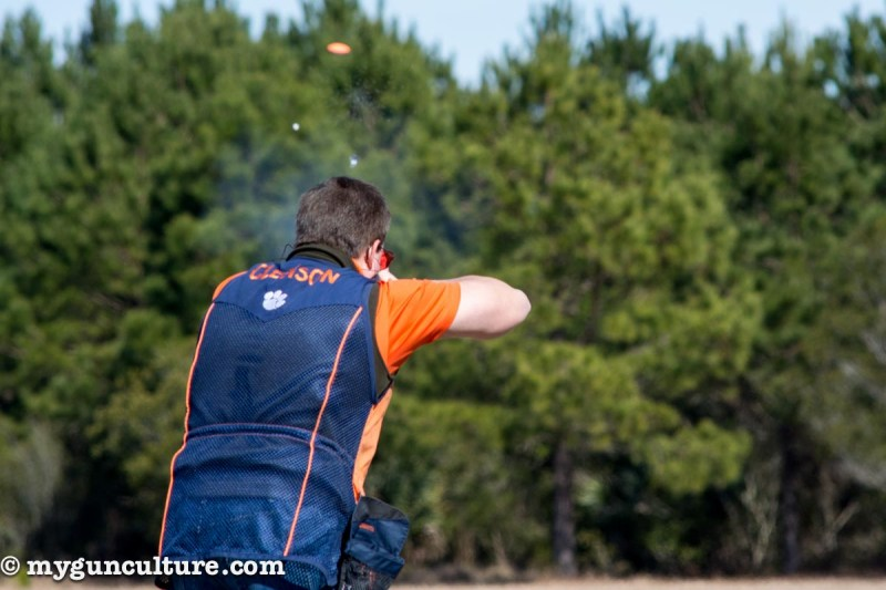 A shot cloud is visible between the top of this shooter's head and the rising trap target.