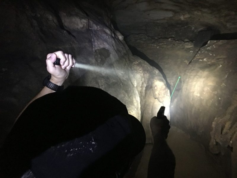 The FBI flashlight technique calls for holding the light out and away from your body, with the lens close to your pinky finger. It arguably provides the most flexibility to searching and navigating with your flashlight.