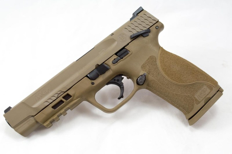 The M&P 9 M2.0 model with 5-inch barrel, flat dark earth Cerakote, and manual safety. The front cocking serrations are subtle; useful for a press check, but out of the way.