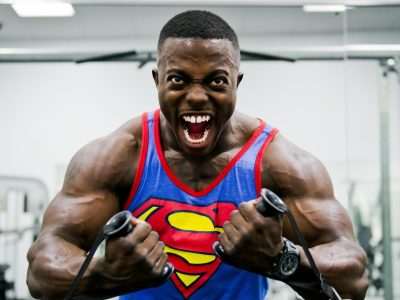a guy pulling weights wearing superman t-shirt in the gym