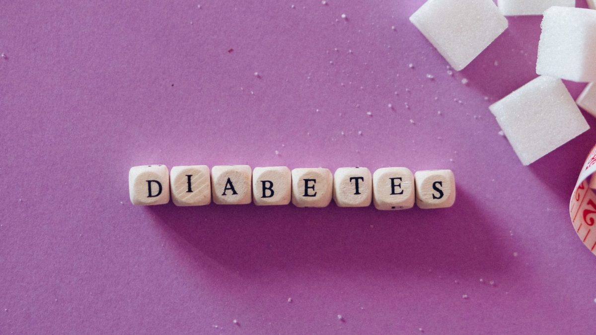 diabetes word blocks hair loss on pink background with sugar cubes